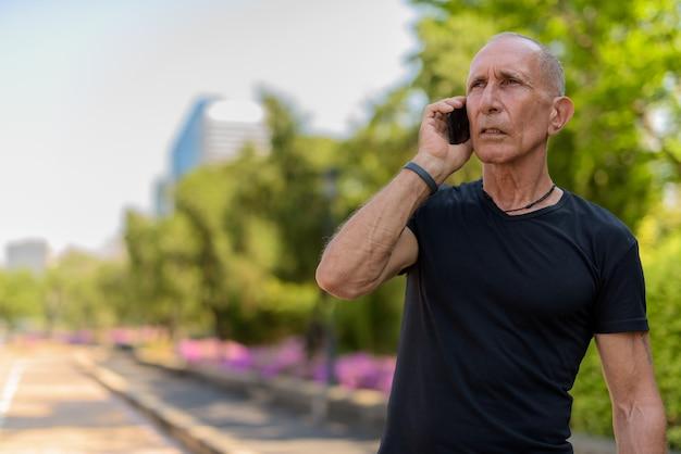 휴대 전화에 말하고있는 동안 생각 대머리 수석 관광 남자는