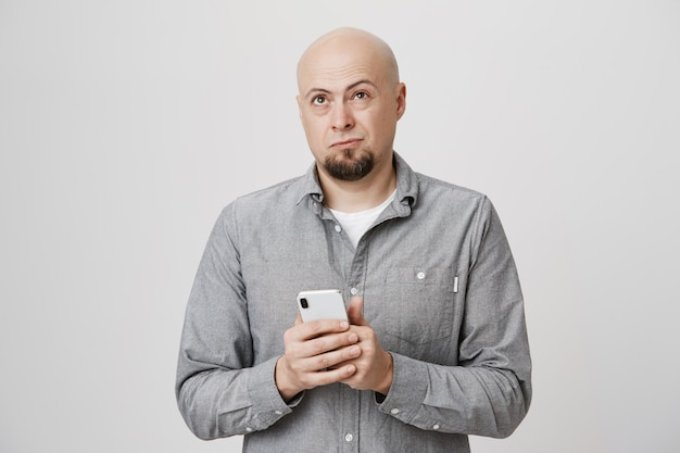 Bald thinking guy looking up, holding mobile phone