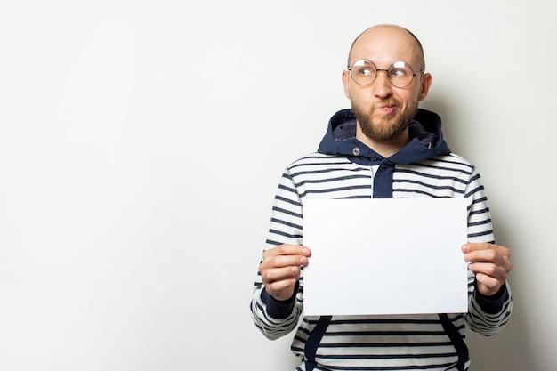 眼鏡のひげを持つハゲの若い男、彼の前に空白の紙のシートを保持しているフード付きのセーター、孤立した白の側にいます。コピースペース