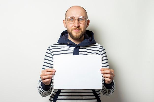 メガネのひげ、分離された白の彼の前に紙の空白のシートを保持しているフード付きのセーターとハゲの若い男。コピースペース