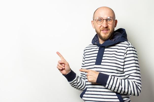 眼鏡のひげを持つハゲの若い男、フード付きのセーターは、孤立した白の側に指を指します。ジェスチャーは注意を払います、これを見てください