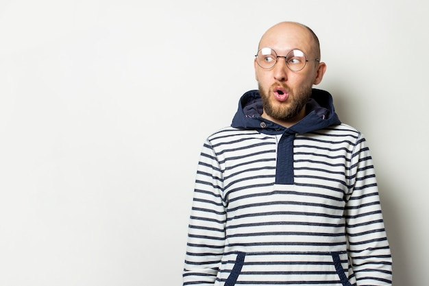 Bald young man with a beard in glasses of a jacket with a hood looks away with a surprised face on an isolated white. gesture of shock, surprise