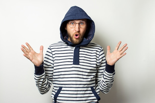 Bald young man with a beard in glasses, a sweater with a hood and a surprised face on an isolated white. man in the hood