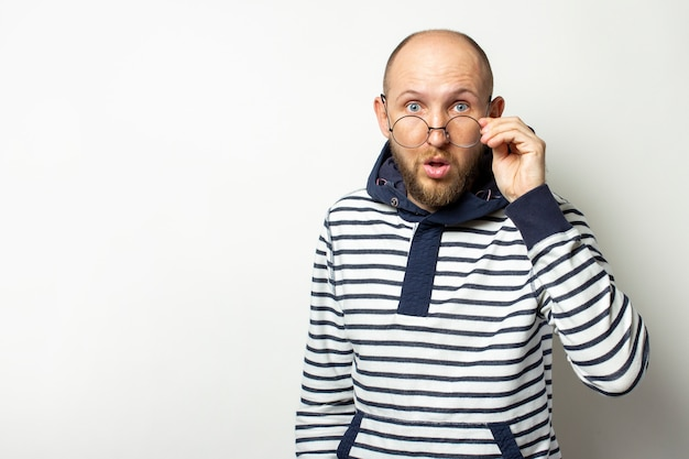 Bald young man with a beard, a sweater with a hood lowered his glasses on his nose with a surprised face on an isolated white. copy space