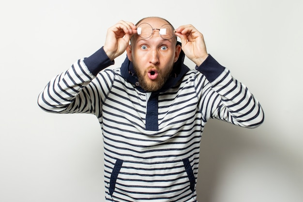 Bald young man with a beard, sweater with hood raised glasses on his forehead with a surprised face on isolated white. gesture of surprise, shock. copy space