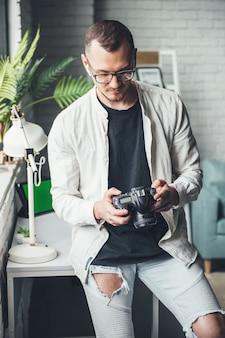 Лысеющий фотограф использует фотоаппарат дома в очках, глядя на экран