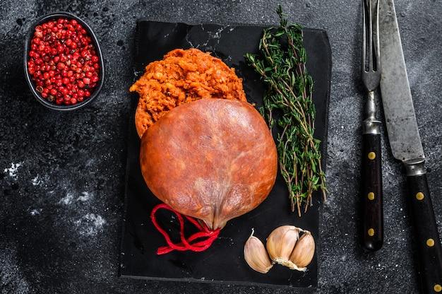 Balearic sobrassada는 갈은 돼지고기, 파프리카 및 향신료로 고기 소시지를 경화시킵니다. 검은 배경. 평면도.