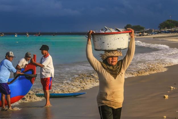Бали, индонезия - 6-ое августа 2017: балийский fishmonger носит рыб в тазе на рынке утра в kedonganan - passer ikan, пляже jimbaran
