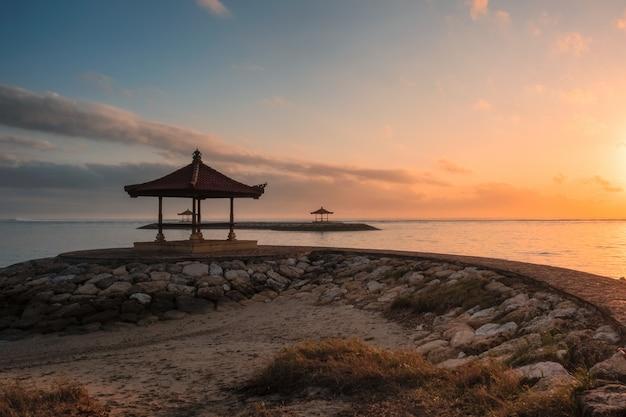 朝の海岸線で桟橋にバリのパビリオン