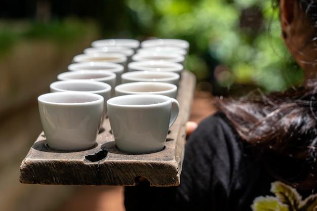 バリの女の子のウェイターは、ウブド、バリ島、インドネシアで味わう観光客のためにさまざまなコーヒーと紅茶を運びます、クローズアップ