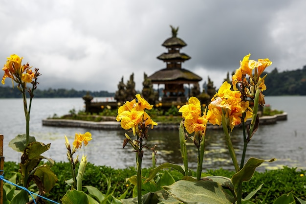Balinese temple on the lake, flowers around.
