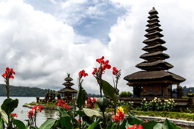 Балийский храм на берегу озера, вокруг цветы.