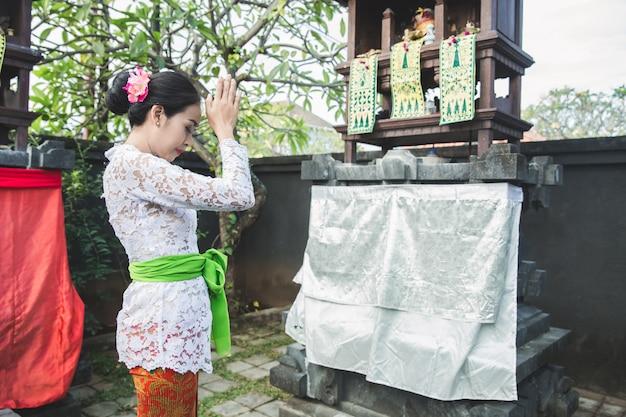 Balinese woman doing ritual offering canang sari and praying