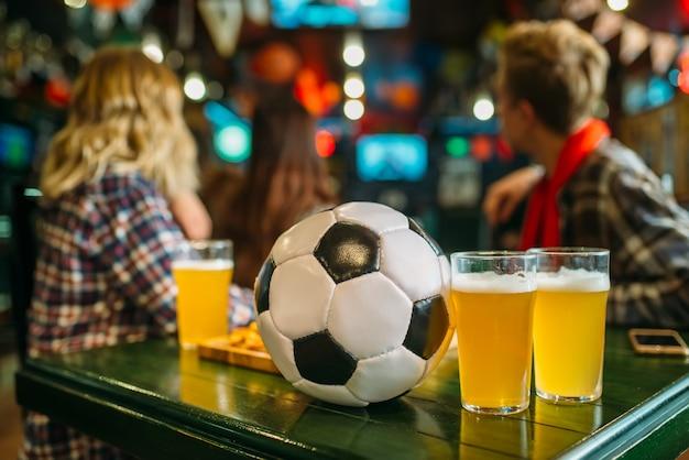 Мяч и пиво на столе в спорт-баре, футбольные фанаты на заднем плане. телетрансляция, просмотр концепции игры