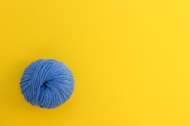 Ball of blue wool yarn on bright yellow background. knitting, handmade and hobby concept