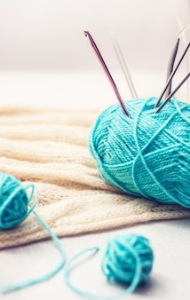 Ball of blue yarn with crochet needle