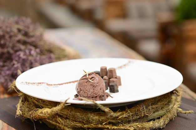 Ball of chocolate ice cream with chocolate pieces on a white plate