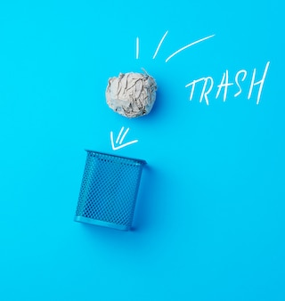 Ball of crumpled gray paper and metal blue wastebasket