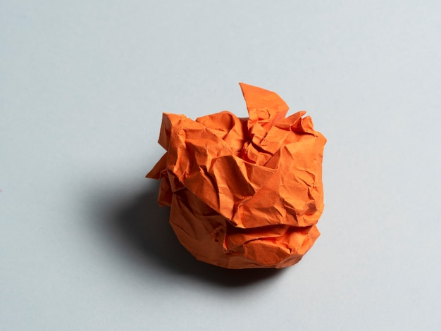 Ball of crumpled orange paper on a light background.