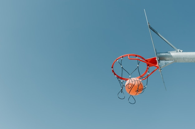 The ball flies into the hoop on an outdoor basketball court in a public park.