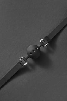 부드러운 그림자와 복사 공간이있는 검정색에 작은 구멍이있는 볼 개그. 에로틱 한 게임에 대한 성적 속성. bdsm 섹스와 에로틱 한 연주 개념.