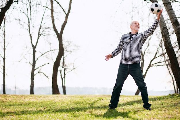 Игра с мячом. радостный зрелый мужчина тренируется с мячом и остается на траве