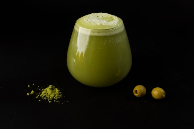 Ball glass with green cocktail, wasabi and olive on black background