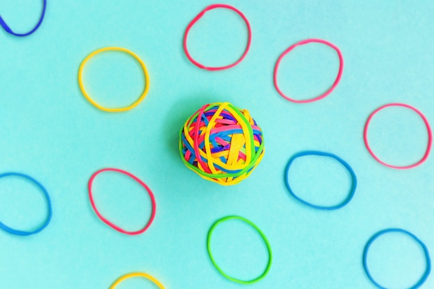 Ball or knot of thin multicolored elastic bands on plain background