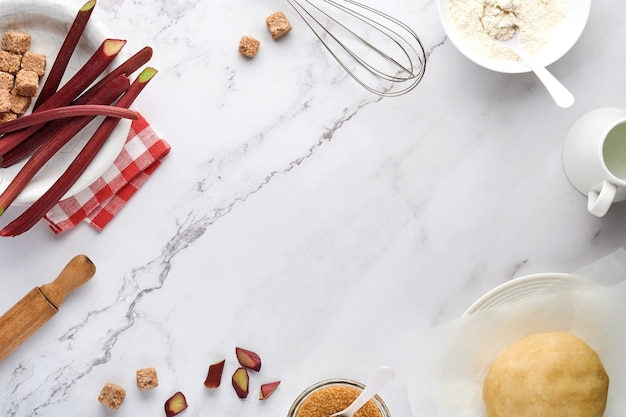 Шарик из теста и ингредиенты мука, вода, масло, сахар и ревень для выпечки на белом