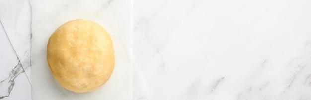 밀가루를 뿌리고 흰색 대리석 배경에 굽기 위한 반죽 공. 단계별 레시피. 선택적 초점입니다. 배너.