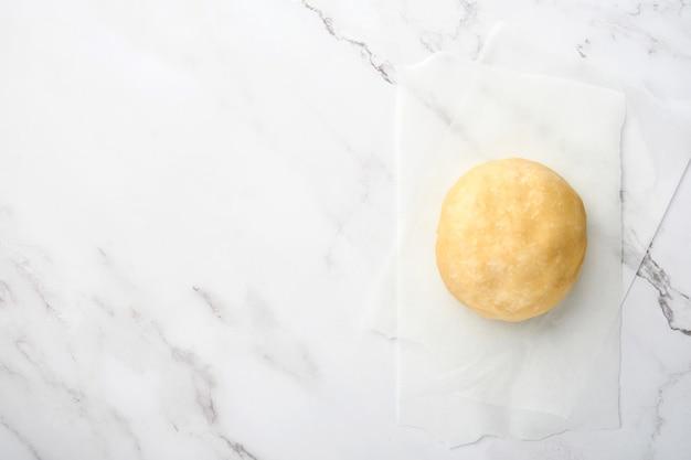 Шарик из теста для выпечки на белом мраморном фоне с присыпкой из муки.