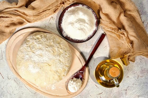 부엌 식탁에 있는 반죽 공은 병에 담긴 올리브 오일로 만든 피자 반죽 소박한 빵을 반죽합니다.