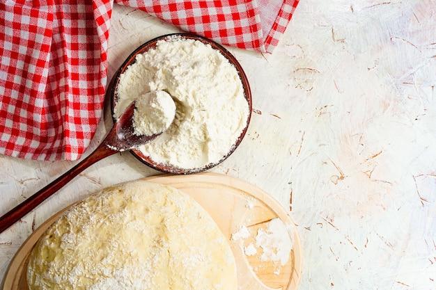 Шарик из теста на белом деревенском столе с мукой в ложке и салфетке скопируйте домашнее тесто для пиццы ...
