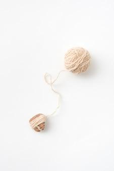흰색 배경에 격리된 수제 뜨개질을 위한 천연 모사 공. 취미와 수공예 작업의 개념.