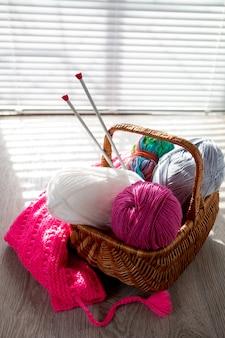 窓の光と木製の灰色のテーブルにバスケットの糸と編み針のボール。閉じる。手作り。