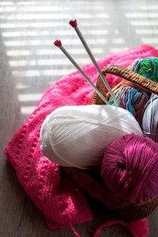 窓の光と木製の灰色のテーブルにバスケットの糸と編み針のボール。手作り。