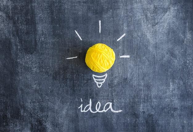 思考のテキストと黄色の糸のボールは、黒板に