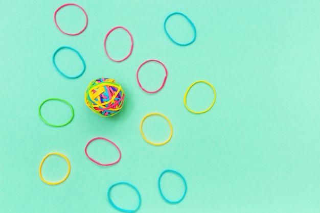 Клубок или узелок из тонких разноцветных резинок на однотонном фоне.