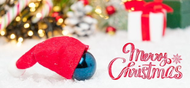 Ball in santa claus hat and merry christmas lettering on the snow