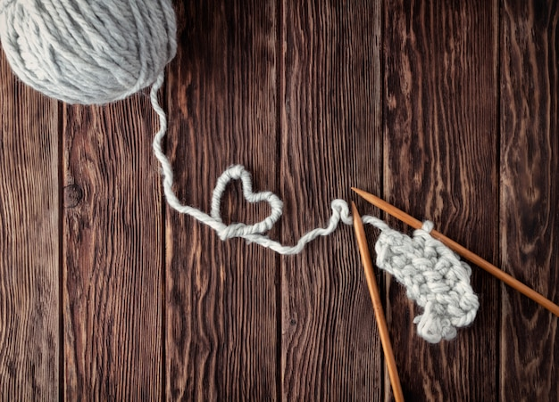 A ball of thread and knitting needles on a wooden background. handmade and needlework concept.