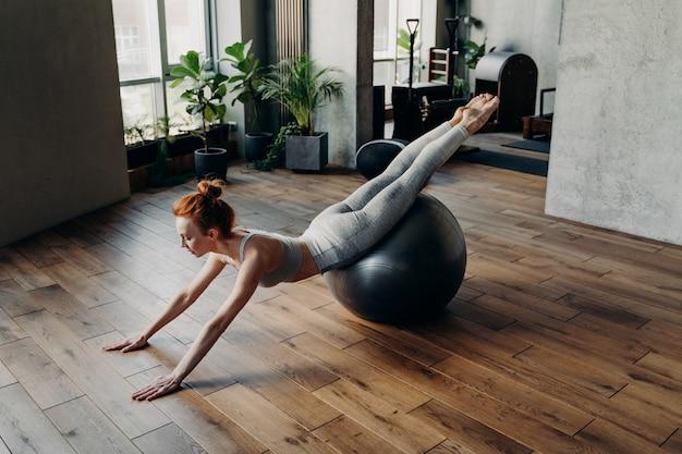 균형과 안정성을 위한 공 운동. 낚시를 좋아하는 젊은 여성이 다리를 꼬고 위쪽으로 향하는 피트볼에 누워 바닥을 기준으로 똑바른 팔로 몸을 지지합니다. 피트니스 개념