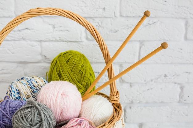 Ball of yarns with crochet in wicker basket