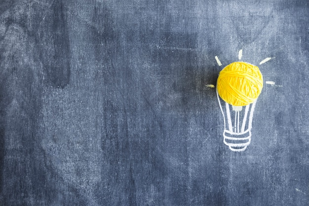 Ball of yellow wool over the hand drawn light bulb on chalkboard