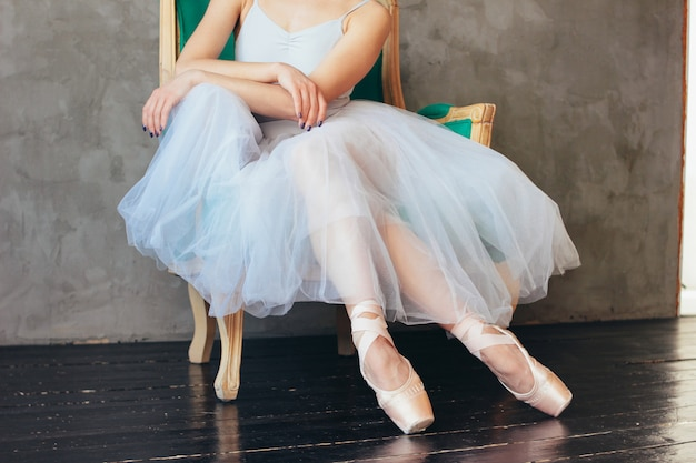The ballerina ballet dancer in tutu skirt and pointe shous sitting on the classic chair