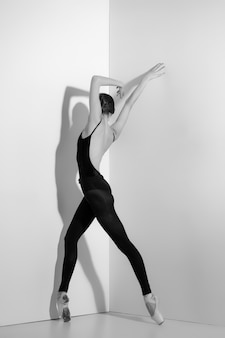 Ballerina in black outfit posing on pointe shoes, studio.