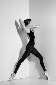 Ballerina in black outfit posing on pointe shoes