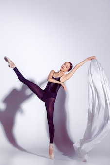Ballerina in black outfit posing on toes, studio background.