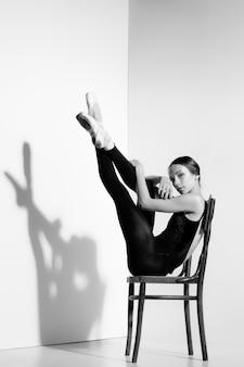 Ballerina in attrezzatura nera che posa su una sedia di legno, studio.