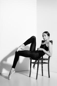 Ballerina in attrezzatura nera che posa su una sedia di legno