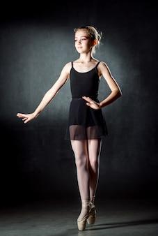 バレリーナ。ポーズとスタジオで踊るかわいい女の子。女の子はバレエを勉強しています。暗い壁。